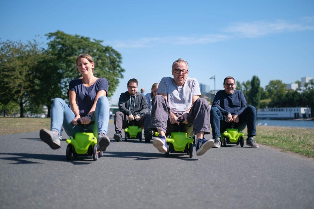Team von Unterschied & Macher machen ein Bobbycar-Rennens am Main